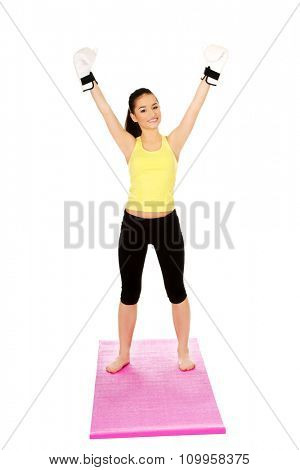 Attractive fitness woman wearing boxing gloves with hands up.