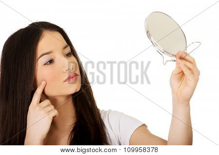 Teenage woman with mirror checking her pimples.