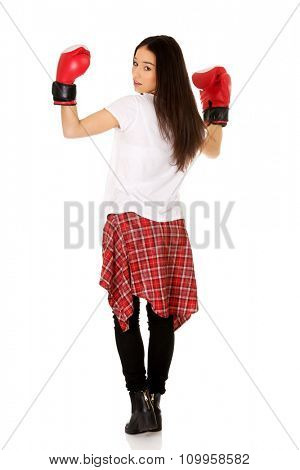 Young teenage woman wearing boxing gloves.