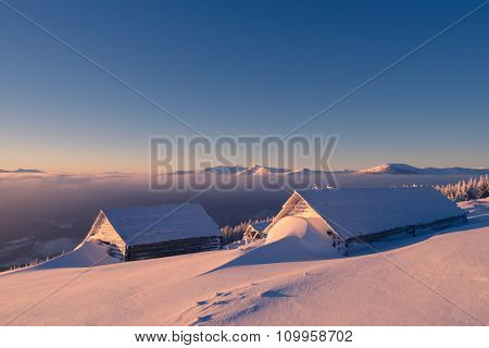 Winter landscape. Wooden houses in snow. Shelter shepherds on hill. Sunny morning in mountains. Carpathians, Ukraine, Europe