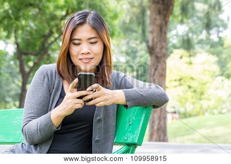 Asian Woman Using Smartphone In The Park
