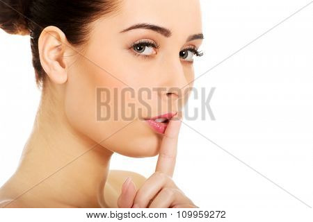 Beautiful glamour woman making hush gesture.
