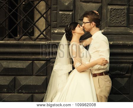 stylish luxury  bride and elegant groom, hugging with tenderness,on the background of the old city Lviv