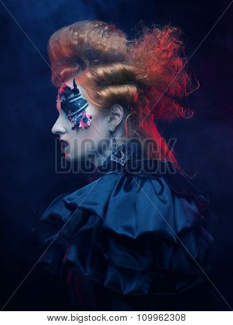 Gothic woman with red hair and bright make up.