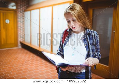 Focused student standing and studying at the university
