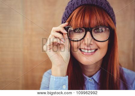Smiling hipster woman looking at camera against wooden background