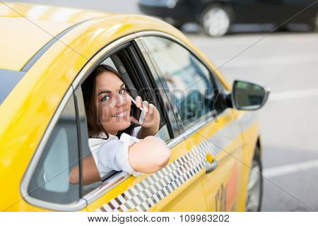 Young female talking on the phone in taxi