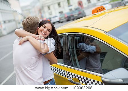 Hugging couple with a taxi