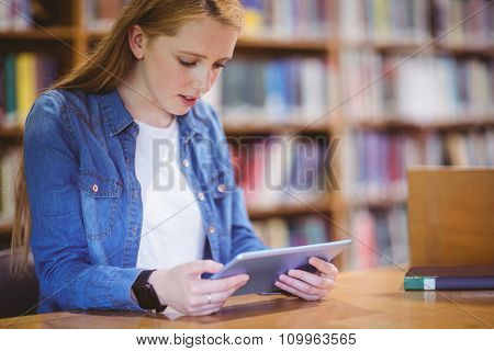 Student with smartwatch using tablet in library at the university