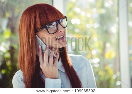 Smiling hipster woman with fringe on phone