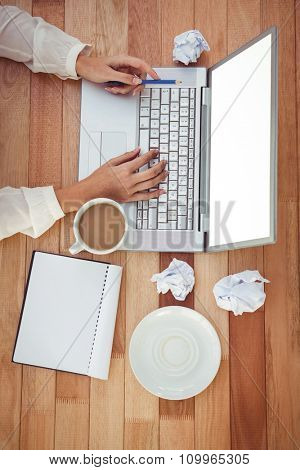 Cropped image of woman with pen using laptop in her office
