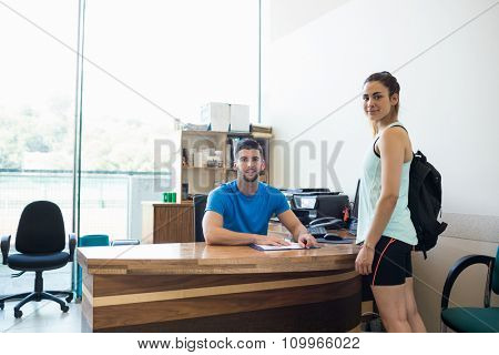 Athletic woman talking with fitness trainer at the gym