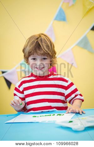 Smiling boy finger painting at the desk