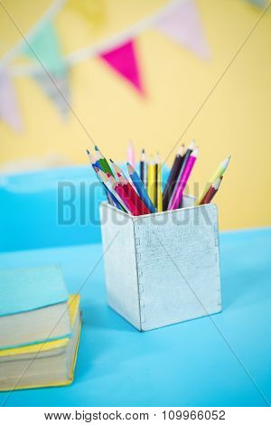 Pencils and books on table in playschool