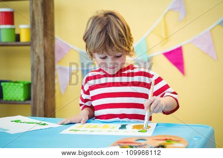 Child painting a beautiful picture at the desk