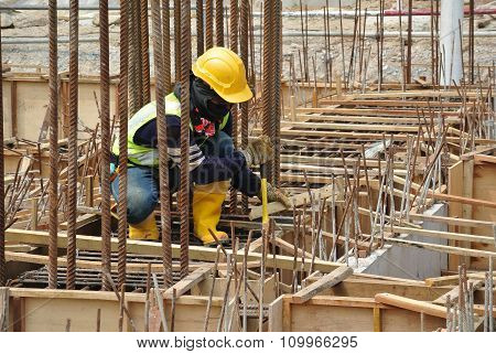 Group of construction workers fabricating ground beam formwork