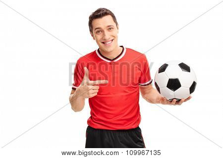 Young football player holding a ball in one hand and pointing towards it with the other isolated on white background
