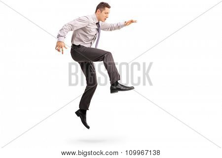Full length profile shot of a young businessman jumping in the air shot in mid-air isolated on white background