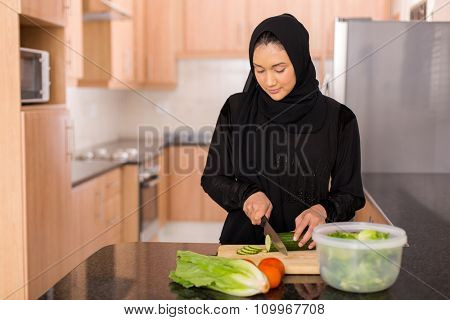 pretty muslim woman chopping vegetables in kitchen