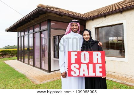 portrait of lovely muslim couple holding for sale sign in front of their house