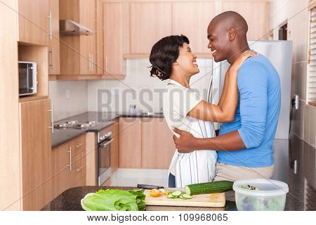 lovely young african couple embracing in kitchen