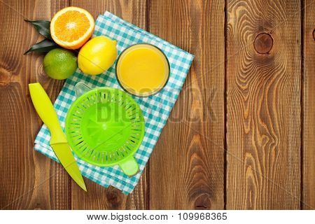 Citrus fruits and glass of juice. Oranges, limes and lemons. Top view over wood table background with copy space