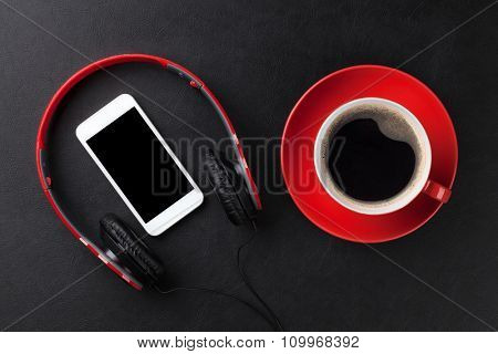 Headphones, smartphone and coffee cup on leather desk table. Top view with copy space