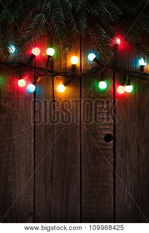 Christmas tree branch and colorful lights on wooden background. View with copy space