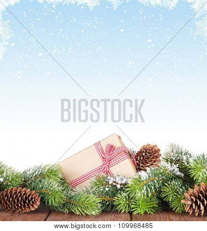 Christmas tree branch on wooden table with snow background for copy space