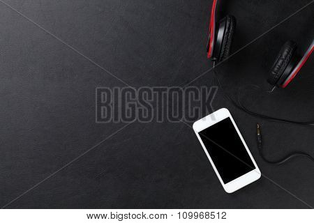 Headphones and smartphone on leather desk table. Top view with copy space