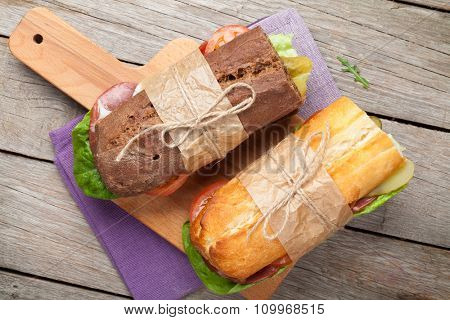 Two sandwiches with salad, ham, cheese and tomatoes on cutting board