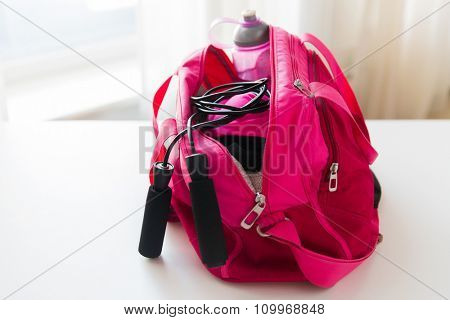 sport, fitness, healthy lifestyle and objects concept - close up of female sports stuff in bag and skipping rope