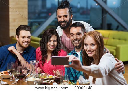 leisure,technology, friendship, people and holidays concept - happy friends having dinner and taking selfie by smartphone at restaurant