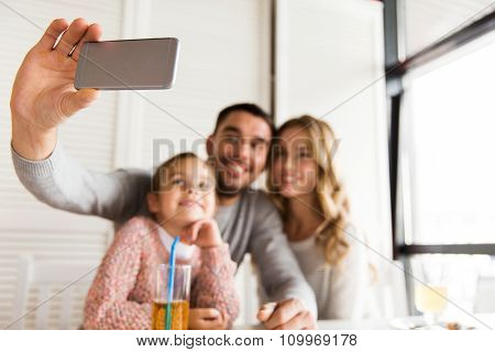 family, parenthood, technology and people concept - close up of happy mother, father and little girl having dinner and taking selfie by smartphone at restaurant