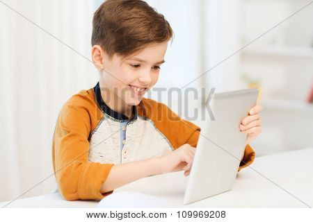 leisure, children, technology and people concept - smiling boy with tablet pc computer at home