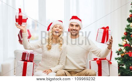 christmas, holidays and people concept - happy couple in santa hats with gift boxes sitting on sofa at home