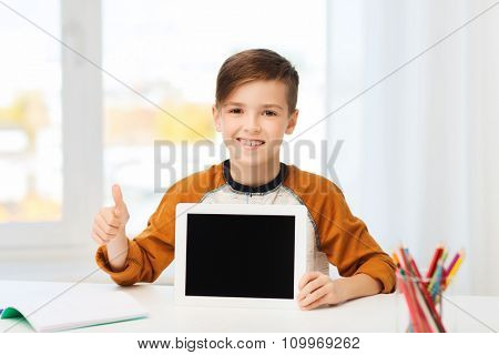 leisure, children, technology, education and people concept - smiling boy showing empty tablet pc computer screen and showing thumbs up at home