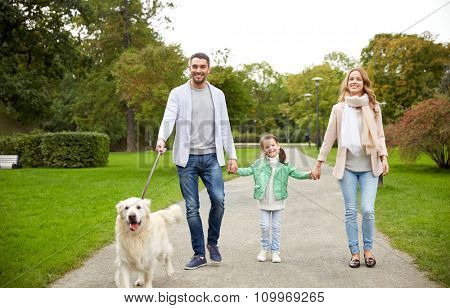 family, pet, domestic animal and people concept - happy family with labrador retriever dog walking in summer park