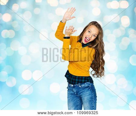 people, style and fashion concept - happy young woman or teen girl in casual clothes having fun and applauding over blue holidays lights background