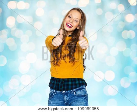people, gesture, style and fashion concept - happy young woman or teen girl in casual clothes showing thumbs up over blue holidays lights background
