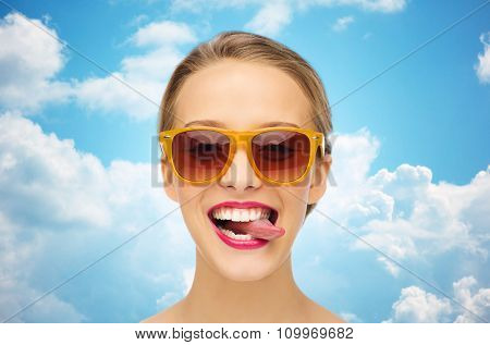 people, expression, joy and fashion concept - smiling young woman in sunglasses with pink lipstick on lips showing tongue over blue sky and clouds background