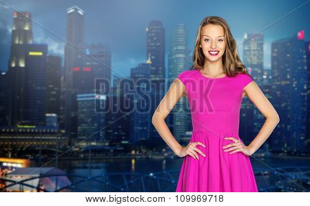 people, style, holidays, nightlife and fashion concept - happy young woman or teen girl in pink dress over night singapore city background