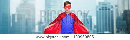 carnival, childhood, power and people concept - happy boy in red super hero cape and mask over city buildings background