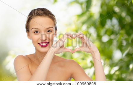 beauty, people, love, valentines day and make up concept - smiling young woman with pink lipstick on lips showing heart shape hand sign over green natural background