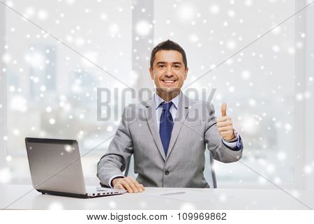 business, people and technology concept - smiling businessman in suit working with laptop computer in office over snow effect