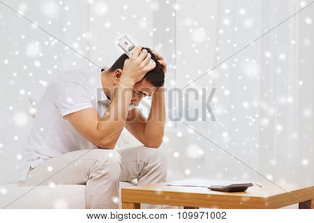 business, savings, financial crisis and people concept - man with money and calculator at home over snow effect
