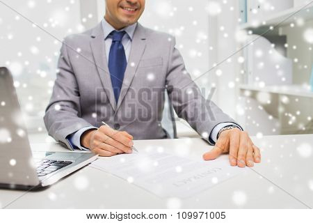 business, people, paperwork and technology concept - close up of smiling businessman with laptop computer and papers working in office over snow effect