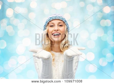 winter, advertisement, christmas and people concept - smiling young woman in winter hat and sweater holding something on her empty palms over blue holidays lights background