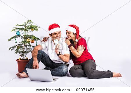 young indian couple with red santa hat, sitting close on white background with christmas tree, succe