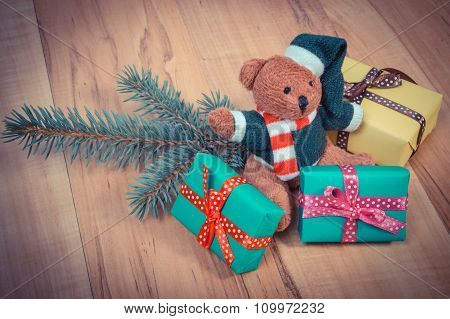 Vintage Photo, Teddy Bear With Colorful Gifts For Christmas And Spruce Branches